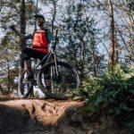 mountainbiker steht auf felsen