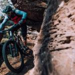 mountainbiker fährt eng am fels